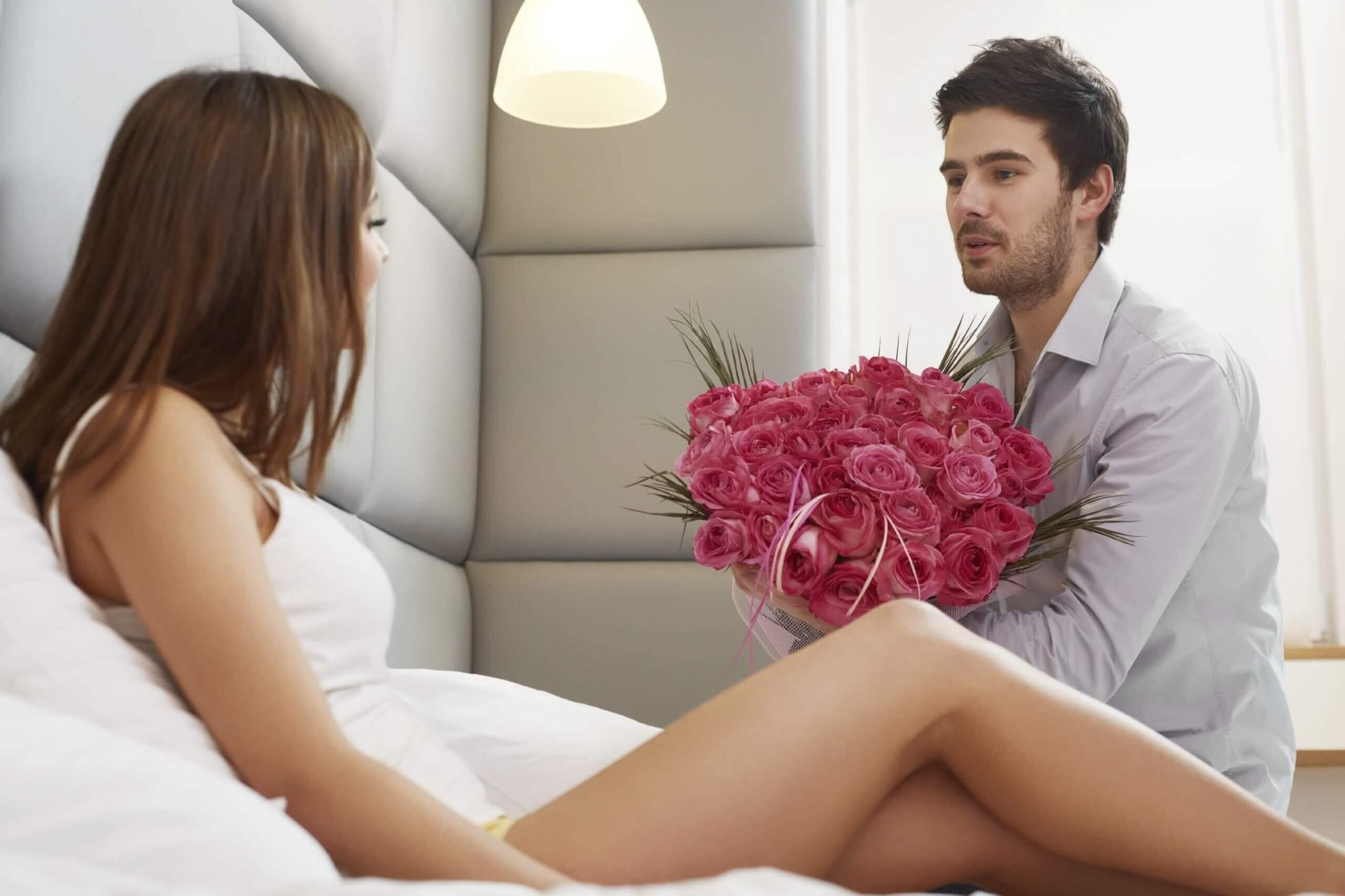мужчина дарит девушке букет цветов в кровати